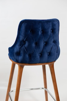 Disparo vertical de una silla azul con botones detrás de un fondo blanco.