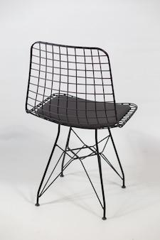 Disparo vertical de una silla futurista con una cadena en la espalda detrás de un fondo blanco.