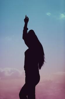 Disparo vertical de una silueta de una mujer bailando durante una hermosa puesta de sol