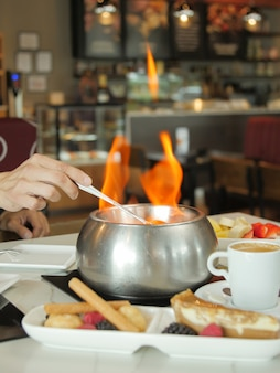 Disparo vertical de una sopa caliente con llamas en una mesa de restaurante