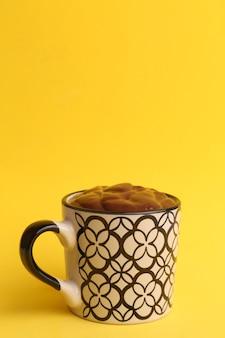 Disparo vertical de una taza de chocolate caliente aislado sobre un fondo amarillo