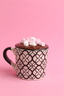 Disparo vertical de una taza de chocolate caliente con malvaviscos aislado sobre un fondo de color rosa