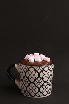 Disparo vertical de taza decorativa con chocolate caliente y malvaviscos sobre un negro