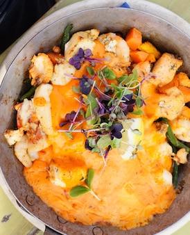Disparo vertical de un tipo de alimento en una olla que contiene verduras
