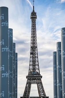 Disparo vertical de una torre eiffel en parís, francia, con un cielo nublado