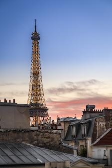Disparo vertical de la torre eiffel durante una puesta de sol rosa en parís, francia
