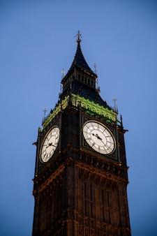 Disparo vertical de la torre del reloj big ben en londres, inglaterra, bajo un cielo despejado