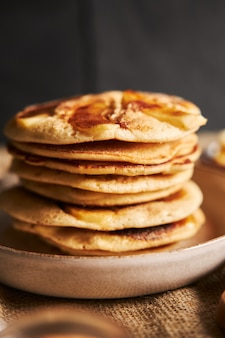 Disparo vertical de tortitas de manzana en un plato sobre un mantel marrón con una pared negra