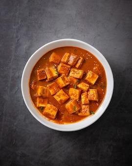 Disparo vertical de la tradicional india paneer mantequilla masala o queso curry sobre una superficie negra