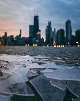 Disparo vertical de trozos de vidrio roto y una moderna ciudad borrosa