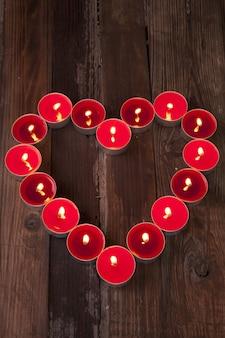Disparo vertical de velas de té encendidas y rojas con forma de corazón sobre una superficie de madera