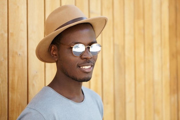 Disparos en la cabeza del atractivo joven afroamericano de aspecto moderno que descansa al aire libre, de pie contra la pared de madera, se siente feliz y relajado, disfruta de días de vacaciones de verano sin preocupaciones