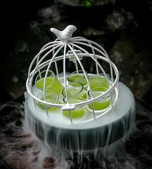 Disparos verdes en una pequeña jaula blanca en un tazón ahumado