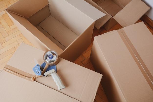 Dispensador de cinta sellando una caja de cartón de envío.