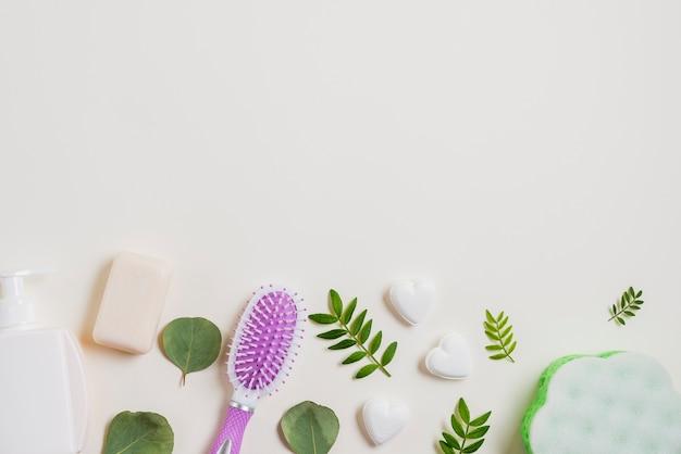 Dispensador; jabón; cepillo para el pelo decorado con hojas sobre fondo blanco
