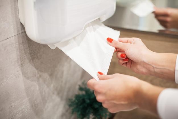 Dispensador de toallas de papel. mano de mujer toma toalla de papel en el baño.