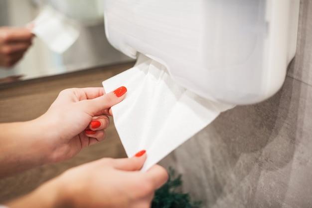 Dispensador de toallas de papel. la mano de la mujer toma la toalla de papel en cuarto de baño.