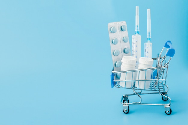 Dispersas píldoras de medicina farmacéutica, tabletas y cápsulas en dinero dólar aislado en la pared azul. gastos de medicina.
