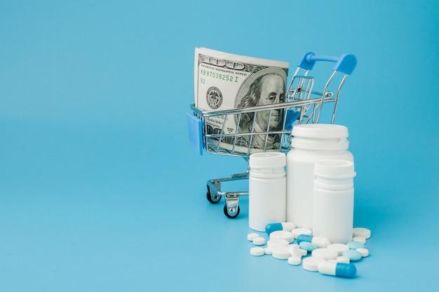 Dispersas píldoras de medicina farmacéutica, tabletas y cápsulas en dinero dólar aislado sobre fondo azul