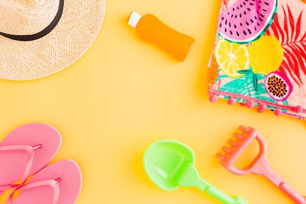 Disposición de accesorios de playa y juguetes infantiles para vacaciones de verano tropical.