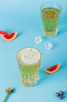 Disposición de alto ángulo con bebidas y rodajas de naranja.