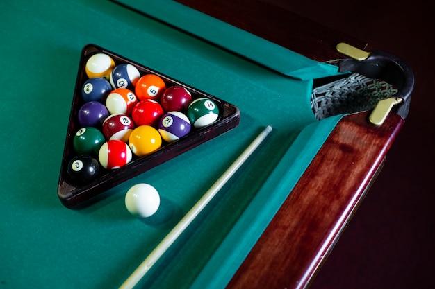 Disposición de alto ángulo con bolas y triángulo en la mesa de billar