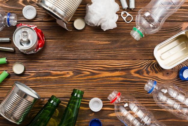 Disposición de basura para reciclaje sobre fondo de madera.