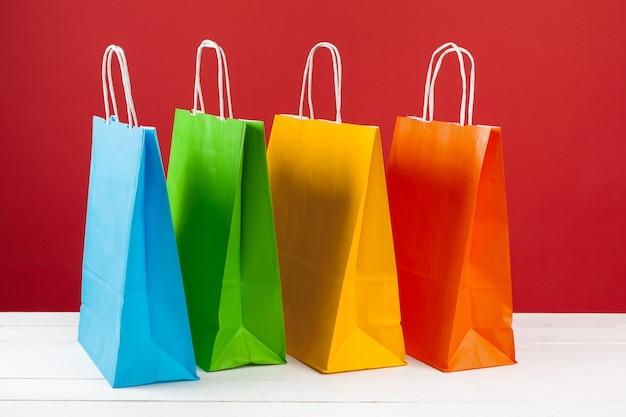 Disposición de bolsas de compras sobre fondo rojo.