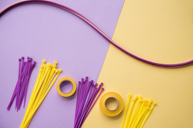 Disposición de cinta aislante y cable de nylon con cremallera sobre fondo doble púrpura y amarillo