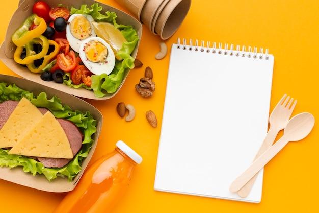 Disposición de las comidas por lotes con el bloc de notas vacío