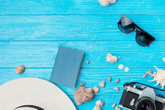 Disposición de conchas cerca de cámara retro y gafas de sol con sombrero