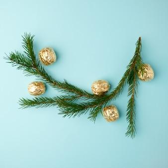 Disposición creativa de chistmas hecha de vegetación de invierno y decoración dorada sobre fondo azul.