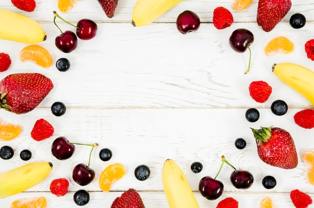 Disposición creativa de frutas sobre fondo de madera.