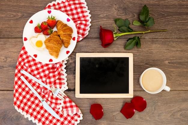 Disposición del desayuno romántico sobre madera.