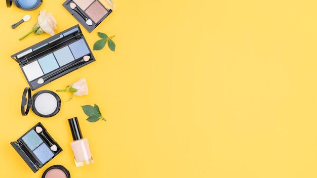 Disposición de diferentes cosméticos con copia espacio sobre fondo amarillo.