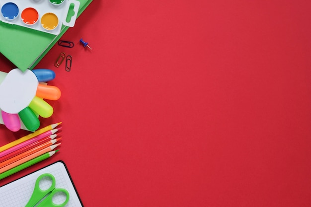Disposición con diversos útiles escolares y papelería sobre fondo rojo.