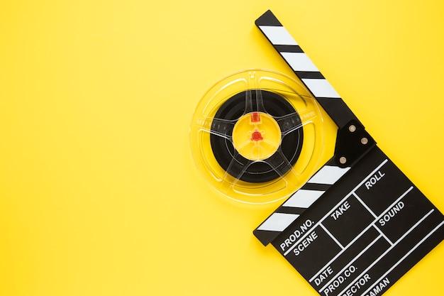 Disposición de elementos de cine sobre fondo amarillo con espacio de copia
