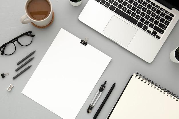 Disposición de elementos de escritorio con cuaderno vacío sobre fondo gris
