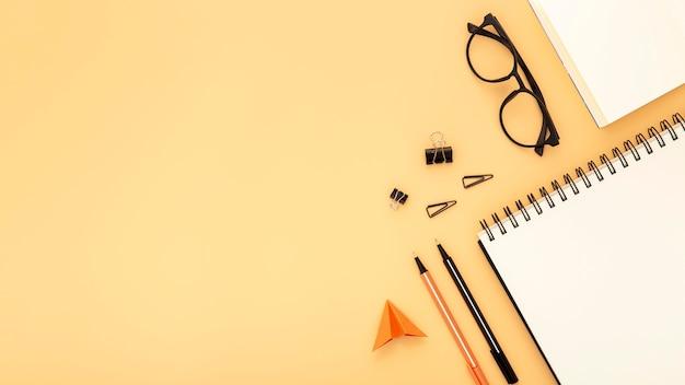 Disposición de elementos de escritorio con espacio de copia sobre fondo naranja