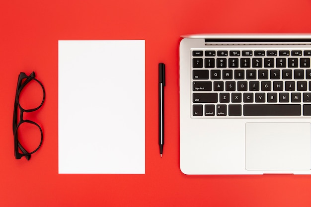 Disposición de elementos de escritorio sobre fondo rojo.