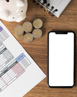 Disposición de elementos financieros con smartphone vacío.