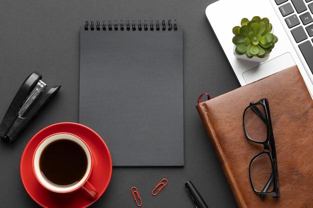 Disposición de elementos de oficina sobre fondo oscuro con bloc de notas
