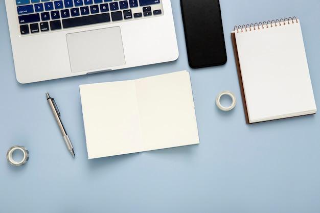 Disposición de escritorio plano con libreta vacía sobre fondo azul.