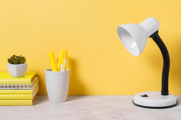 Disposición del espacio de trabajo con libros y lámpara.