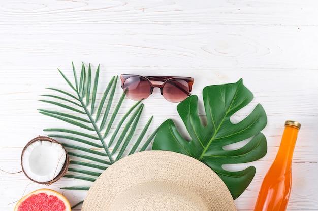 Disposición exótica de vacaciones de hojas con gafas de sol.