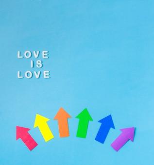 Disposición de las flechas de papel en colores lgbt y el amor es palabras de amor