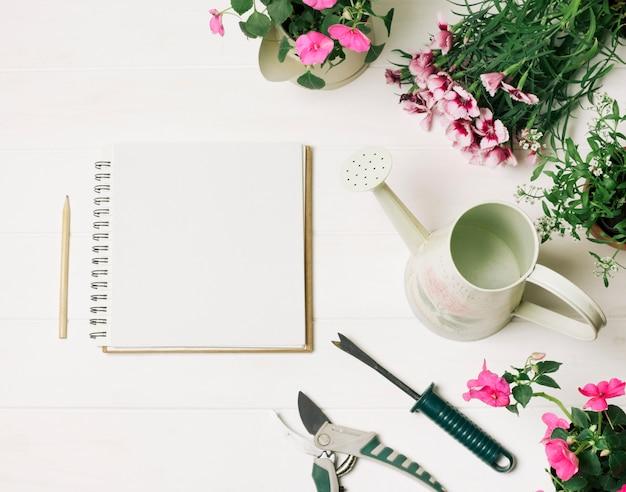 Disposición de flores y bloc de notas.