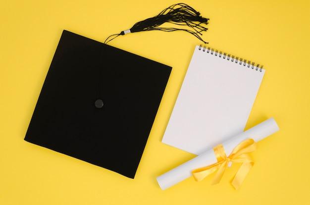Disposición de graduación festiva plana con libreta vacía