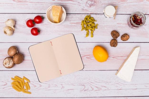 Disposición del ingrediente de pasta y diario abierto en blanco en el escritorio de madera