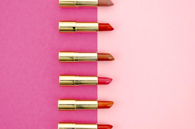Disposición minimalista de lápices labiales sobre fondo rosa